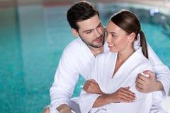 glückliche junge Paare in den Bademäntel, die nahe Pool umfassen stockbilder