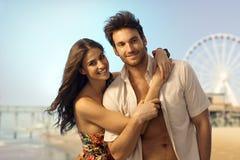 Glückliche junge Paare an den sandigen Sommerferien setzen auf den Strand Stockfotos