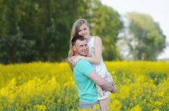Glückliche junge Paare in der Liebe, die auf dem gelben Rapsgebiet umarmt stockbild