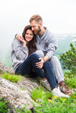 Glückliche junge Paare in der Liebe, die auf einem Berg, einem Umarmen und einem lo sitzt Stockfoto