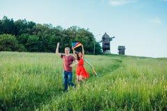 Glückliche junge Paare in der Liebe, die einen Drachen auf dem Feld laufen lässt Zwei, Mann und Frau lächelnd und in der Landseit Stockbilder