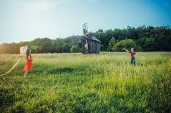 Glückliche junge Paare in der Liebe, die einen Drachen auf dem Feld laufen lässt Zwei, Mann und Frau lächelnd und in der Landseit Stockfotografie