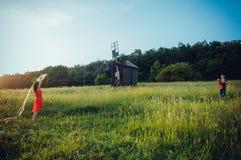 Glückliche junge Paare in der Liebe, die einen Drachen auf dem Feld laufen lässt Zwei, Mann und Frau lächelnd und in der countriy Lizenzfreies Stockbild