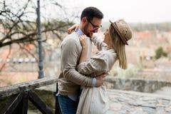 Glückliche junge Paare in der Liebe, die im Freien umarmt und lächelt stockfoto