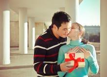Glückliche junge Paare in der Liebe mit Geschenk draußen Lizenzfreie Stockfotos
