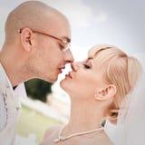 Glückliche junge Paare des Braut- und Bräutigamküssens Stockbild
