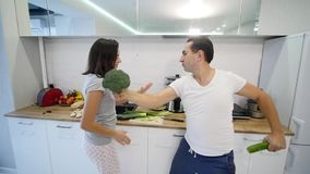 Glückliche junge Paare des Morgens zu Hause heiraten eben das Tanzen, das Musik in tragenden Pyjamas der Küche hört Langsame Bewe stock video
