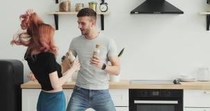 Glückliche junge Paare des Morgens zu Hause heiraten eben das Tanzen, das Musik in tragenden Pyjamas der Küche in der Liebe hört, stock footage