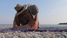 Glückliche junge Paare, die auf dem Strand, zurück liegend auf ihr und Küssen ein Sonnenbad nehmen stock video