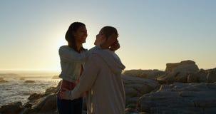 Glückliche junge Paare, die auf einander auf felsigem Ufer 4k einwirken stock video
