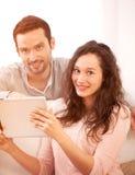 Glückliche junge Paare, die auf eine Tablette surfen stockfotografie