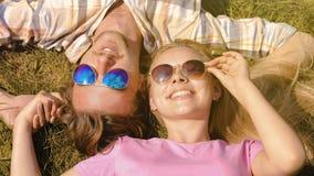 Glückliche junge Paare, die auf Rasen, Händchenhalten, Wochenende am Sommertag genießend liegen stockbilder