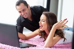 Glückliche junge Paare, die auf Teppich über Tablette lachen Stockbilder