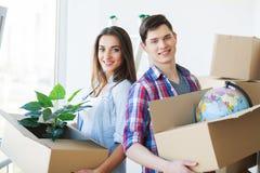 Glückliche junge Paare, die auspacken oder Verpackungskästen und in a, die sich bewegen lizenzfreie stockbilder