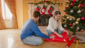 Glückliche junge Paare, die das Weihnachtsgeschenke und Küssen einwickeln stock video