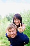 Glückliche junge Paare, die Daumen zeigen Stockbild