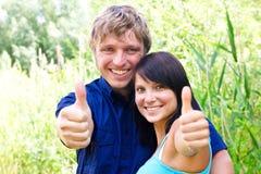 Glückliche junge Paare, die Daumen zeigen Stockfotos