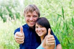 Glückliche junge Paare, die Daumen zeigen Lizenzfreies Stockbild