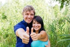 Glückliche junge Paare, die Daumen zeigen Lizenzfreie Stockbilder