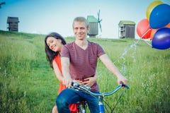 Glückliche junge Paare, die den Spaß draußen anstrebt eine Fahrt mit dem Fahrrad in der Landschaft haben Lizenzfreie Stockfotografie