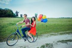 Glückliche junge Paare, die den Spaß draußen anstrebt eine Fahrt mit dem Fahrrad in der Landschaft haben Lizenzfreies Stockbild