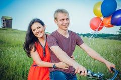Glückliche junge Paare, die den Spaß draußen anstrebt eine Fahrt mit dem Fahrrad in der Landschaft haben Stockfotografie