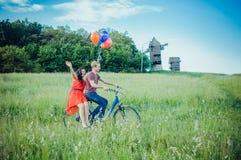 Glückliche junge Paare, die den Spaß draußen anstrebt eine Fahrt mit dem Fahrrad in der Landschaft haben Stockbilder
