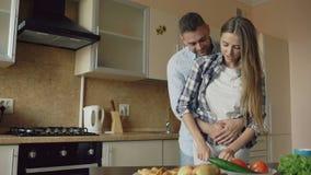 Glückliche junge Paare, die in der Küche beim Frühstück zu Hause kochen umfassen und sprechen stock video