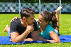 Glückliche junge Paare, die die Sonne genießend sich entspannen Stockbilder