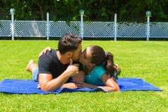 Glückliche junge Paare, die die Sonne genießend sich entspannen stockfoto