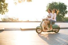 Glückliche junge Paare, die draußen einen Roller reiten Stockfotografie