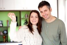 Glückliche junge Paare, die in ein neues Haus sich bewegen Stockfotografie