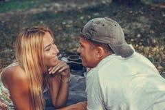 Glückliche junge Paare, die ein Picknick im Park an einem sonnigen Tag haben stockbilder