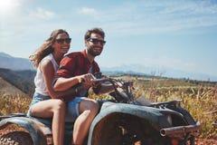 Glückliche junge Paare, die ein Viererkabelfahrrad fahren stockfotografie