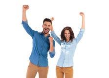 Glückliche junge Paare, die Erfolg mit den Händen oben feiern lizenzfreie stockbilder