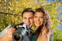 Glückliche junge Paare, die Kamera betrachten Stockfotografie