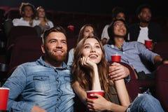 Glückliche junge Paare, die am Kino sitzen lizenzfreies stockfoto