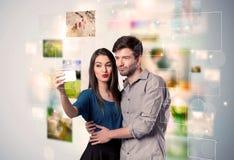 Glückliche junge Paare, die selfie Fotos machen Lizenzfreie Stockfotos