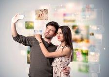 Glückliche junge Paare, die selfie Fotos machen Lizenzfreie Stockbilder