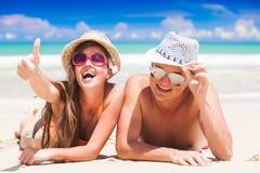 Glückliche junge Paare, die Spaß auf einem tropischen Strand liegen und haben Stockfotografie