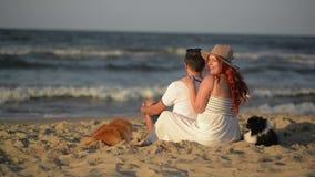 Glückliche junge Paare, die Spaß draußen und das Lächeln haben Schöne Paare, die auf Strand am Abend legen Leute stock video footage
