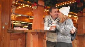 Glückliche junge Paare, die Spaß haben und auf dem Weihnachtsmarkt, der schönen Familie zusammen kühlen und dem Trinken küssen stock video