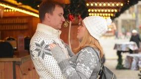 Glückliche junge Paare, die Spaß haben und auf dem Weihnachtsmarkt, schöne Familie zusammen kühlt auf der Weihnachtsmesse küssen stock video footage
