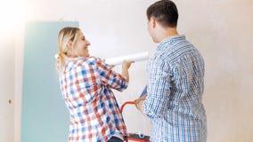 Glückliche junge Paare, die Tapeten für Erneuerung im Haus wählen Lizenzfreie Stockfotos