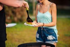 Glückliche junge Paare, die Treffen braten und draußen Hamburger machen Lizenzfreie Stockbilder