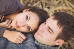 Glückliche junge Paare, die unten liegen, lächelnd am Herbsthintergrund Stockfotos