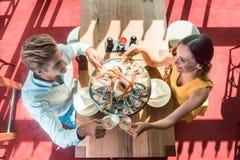 Glückliche junge Paare, die während des romantischen Abendessens an einem modischen Restaurant rösten Stockbilder