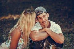 Gl?ckliche junge Paare, die w?hrend des romantischen Picknicks in einem Park genie?en lizenzfreies stockfoto