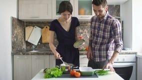 Glückliche junge Paare, die zu Hause in der modernen Küche kochen stock video