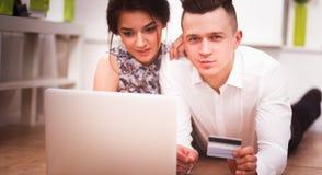 Glückliche junge Paare, die zusammen auf dem Boden mit Laptop sitzen Stockfoto